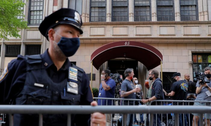 An officer from the New York Police Department places barricades outside the apartment building of former New York City Mayor Rudy Giuliani, personal attorney to former President Donald Trump, in New York City, on April 28, 2021. (Andrew Kelly/Reuters)