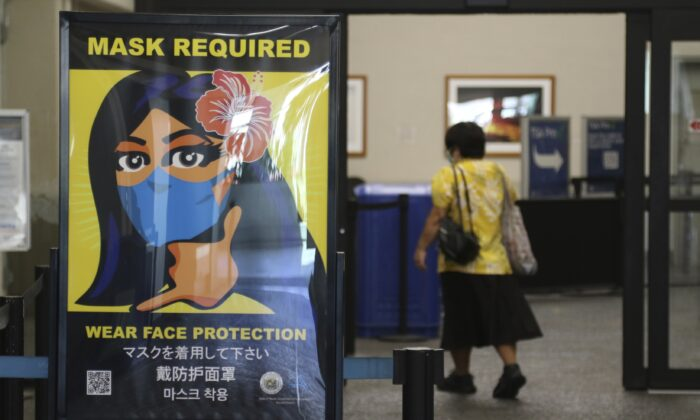 A woman walks into the international airport in Honolulu amid a quarantine rule that effectively shut down the tourism industry in the state on Oct. 2, 2020. (Caleb Jones/ AP Photo)