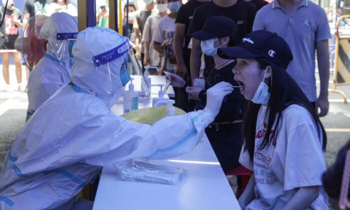 A woman (R) receives a nucleic acid test for the COVID-19 virus in Guangzhou, China, on May 30, 2021. (AFP via Getty Images)