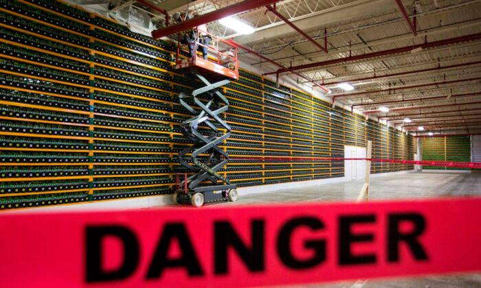 Two construction workers use a lift along a wall of bitcoin mining at Bitfarms in Saint Hyacinthe, Quebec, on March 19, 2018. (Lars Hagberg/AFP via Getty Images)