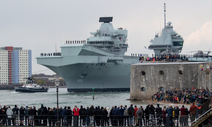 The Royal Navy aircraft carrier HMS Queen Elizabeth passes the Round Tower as it leaves Portsmouth Naval Base in Hampshire for exercises off Scotland before heading to the Indo-Pacific region, on May 1, 2021. (PA)