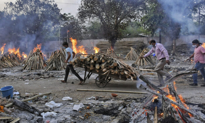 A worker carries wood on a hand cart as multiple funeral pyres of COVID-19 victims burn at a crematorium on the outskirts of New Delhi, India, on May 1, 2021. (Ishant Chauhan/AP Photo)