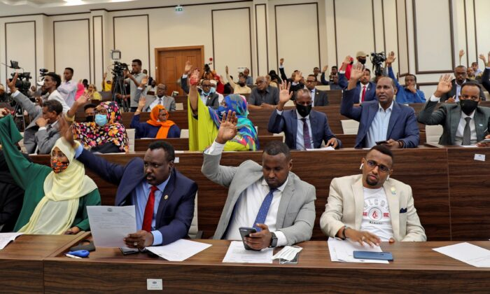 Somalia legislators vote by rising their hands to cancel a divisive two-year presidential term extension, inside the lower house of Parliament in Mogadishu, Somalia, on May 1, 2021. (Feisal Omar/Reuters)
