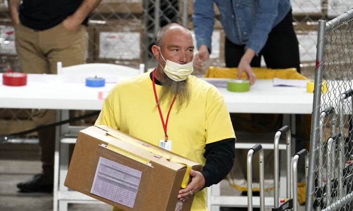 A box of ballots cast in the 2020 election are delivered to be examined and recounted by contractors working for Florida-based company, Cyber Ninjas, who was hired by the Arizona Senate, at Veterans Memorial Coliseum in Phoenix, Ariz., on April 29, 2021. (Rob Schumacher/The Arizona Republic via AP/Pool)