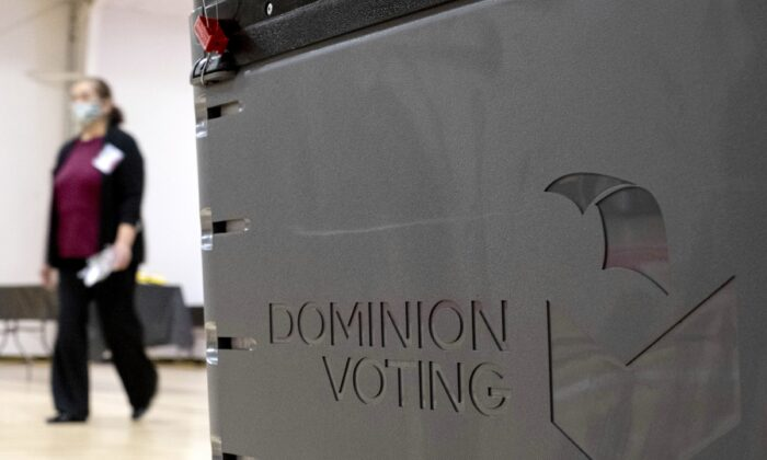 A worker passes a Dominion Voting ballot scanner while setting up a polling location at an elementary school in Gwinnett County, Ga., outside of Atlanta on Jan. 4, 2021. (Ben Gray/AP Photo)