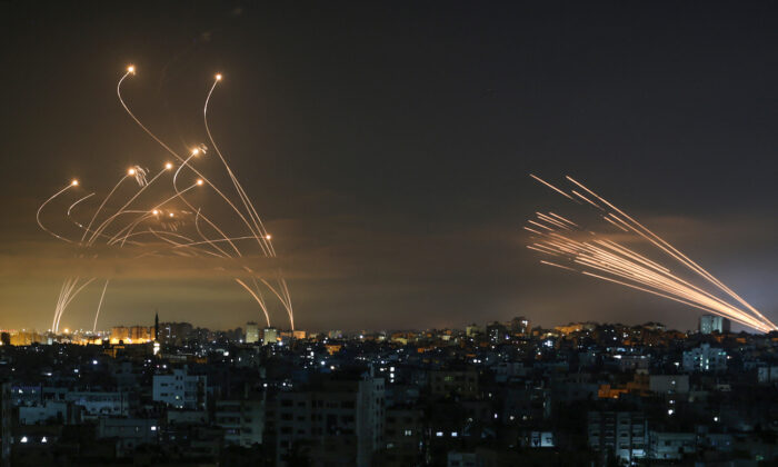 Israel's Iron Dome missile defense system (L) intercepts rockets (R) fired by the Hamas movement toward southern Israel from Beit Lahia in the northern Gaza Strip as seen in the sky above the Gaza Strip overnight on May 14, 2021. (Anas Baba/AFP via Getty Images)
