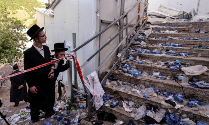 Ultra Orthodox Jews look at stairs with waste on it in Mount Meron, northern Israel, where fatalities were reported among the thousands of ultra-Orthodox Jews gathered at the tomb of a 2nd-century sage for annual commemorations that include all-night prayer and dance, on April 30, 2021. (Ronen Zvulun/Reuters)