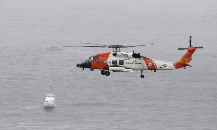 A U.S. Coast Guard helicopter flies over boats searching the area where a boat capsized just off the San Diego coast, in San Diego, on May 2, 2021. (Denis Poroy/AP Photo)