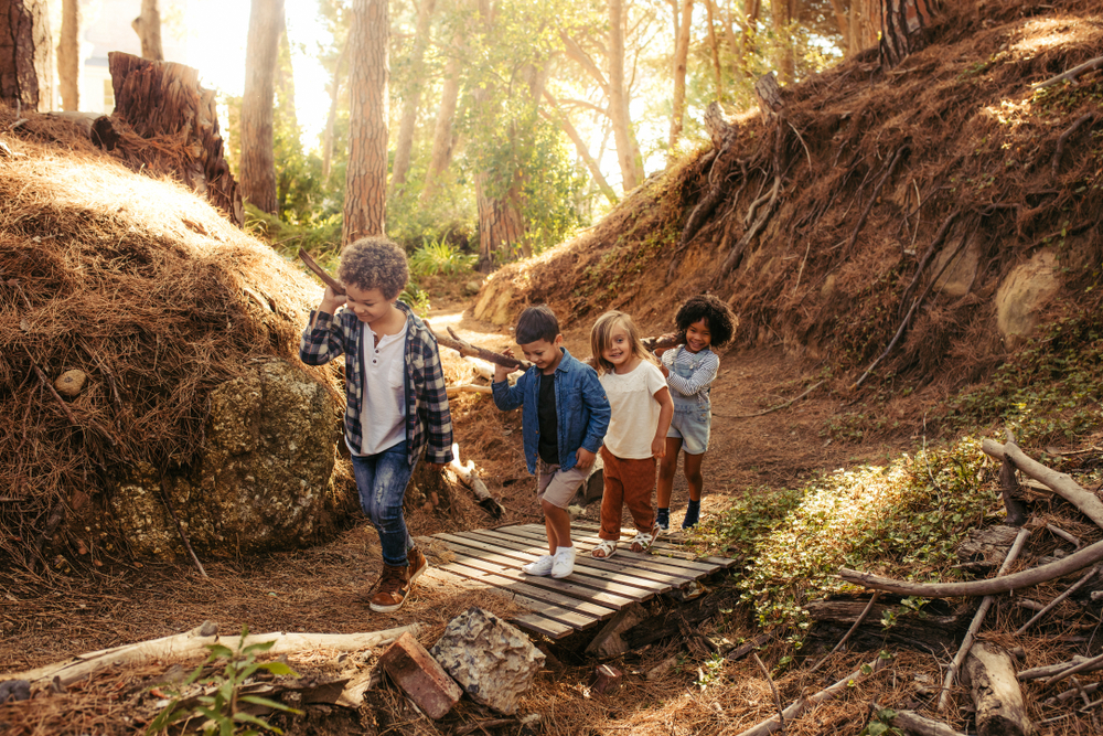 Group,Of,Children,Building,Camp,In,Forest,Together.,Boys,And