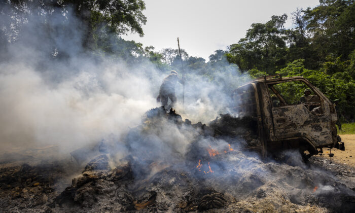 Congolese Army soldiers and UN forces inspect an ambush site where an hour previously ADF fundamentalist rebels attacked two vehicles on the road between Beni and the Ugandan border town of Kasindi, in Kilya, Rwenzori Sector, Democratic Republic of Congo, on April 9, 2021. (Brent Stirton/Getty Images)