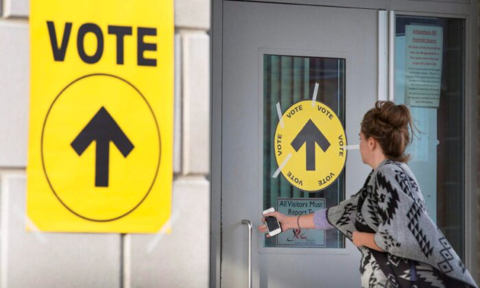 A woman enters a polling place to cast her vote in the federal election on Oct. 19, 2015. (The Canadian Press/Peter Power)