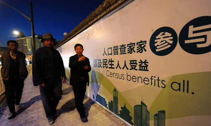 Pedestrians walk past a billboard for China's coming census in Beijing on Oct. 29, 2010. (Frederic J. Brown/AFP via Getty Images)