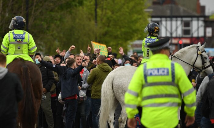 Police move people away from the stadium after a supporter's protest against Manchester United's owners, outside English Premier League club Manchester United's Old Trafford stadium in Manchester, northwest England, on May 2, 2021. (Oli Scarff/AFP via Getty Images)