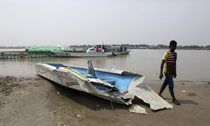 A man walks past the mangled remains of a speedboat that overturned in River Padma at the Kanthalbari ferry terminal in Madaripur, central Bangladesh, on  May 3, 2021. (Abdul Goni/AP Photo)