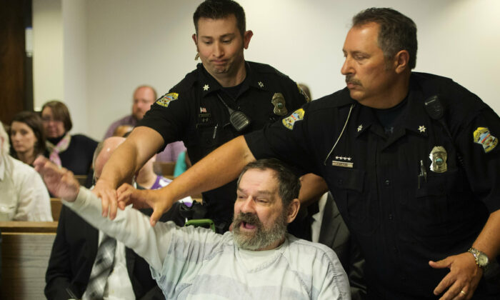 Frazier Glenn Miller Jr., convicted of capital murder, attempted murder and other charges, gestures as Johnson County deputies remove Miller from the courtroom during the sentencing phase of his trial at the Johnson County District Court in Olathe, Kan., on Nov. 10, 2015. (Joe Ledford/Pool/The Kansas City Star via AP)