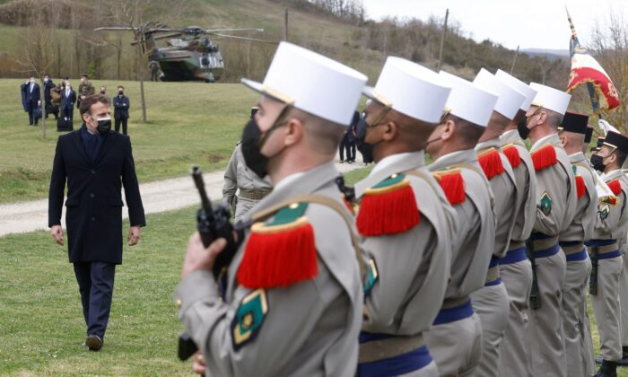 French President Emmanuel Macron reviews soldiers of the 4th Regiment during a military honors ceremony at  the 4th Regiment of the Foreign Legion's training center in La Ferme du Cuin, in Saint-Gauderic, France, on March 12, 2021. (Stephane Mahe/X02520/AFP via Getty Images)