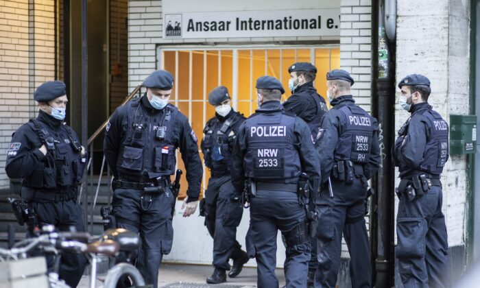 Police officers stay in front of a building of the Ansaar International association in Duesseldorf, Germany, on May 5, 2021. (Marcel Kusch/dpa via AP)