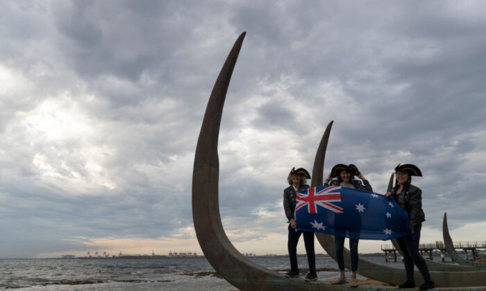 Three women wave the Australian flag at a new installation at the site Lieutenant James Cook is believed to have first stepped ashore on April 29, 2020 in Sydney, Australia. (Brook Mitchell/Getty Images)