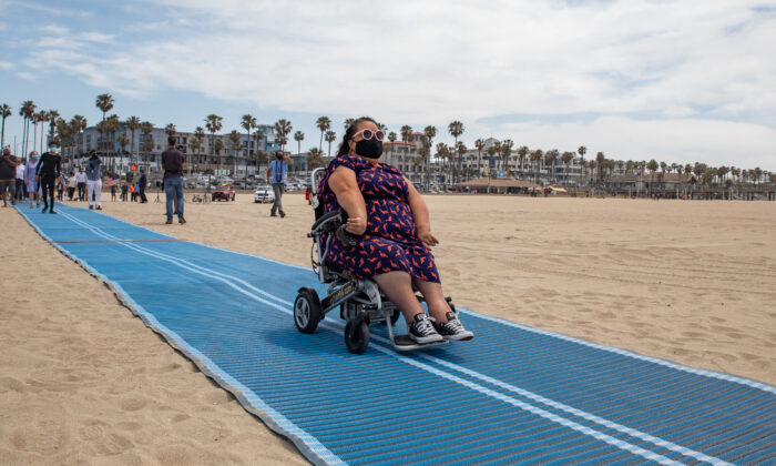 The City of Huntington Beach, Calif., celebrates the release of its first Mobi-Mat, a wheelchair accessible pathway that leads from the boardwalk to the ocean, on May 5, 2021. (John Fredricks/The Epoch Times)