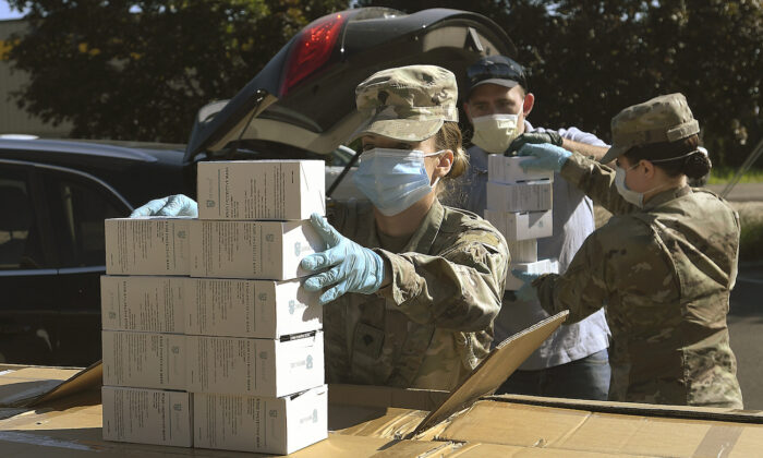 An Oregon National Guard member counts out boxes of face masks while participating in a distribution event at the Oregon State University Extension Service-Linn County office in Tangent, Ore., on May 27, 2020. (Mark Ylen/Albany Democrat-Herald via AP)