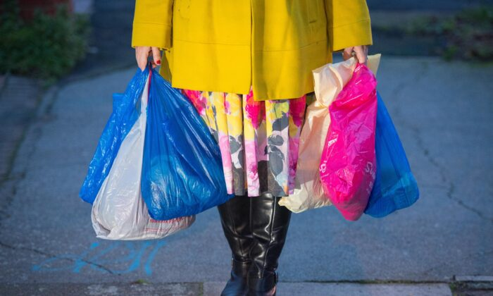 A shopping being carried in plastic carrier bags. Picture issued on May 7, 2021. (PA)