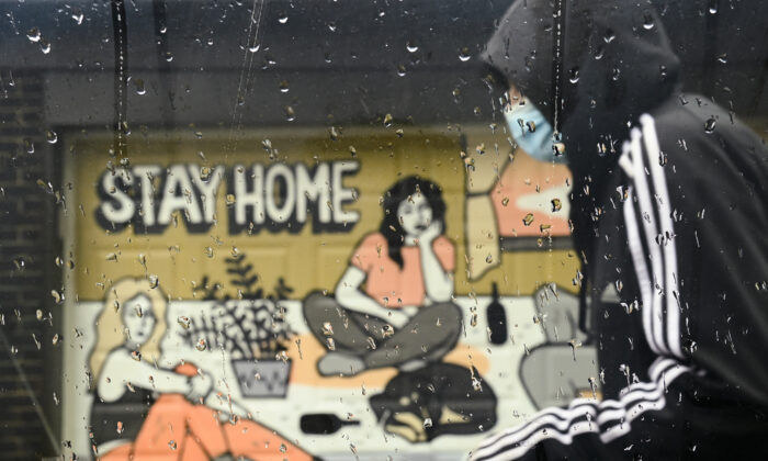 A person walks past a COVID-19 mural designed by artist Emily May Rose on a rainy day during the COVID-19 pandemic in Toronto, Canada, on April 12, 2021. (Nathan Denette/The Canadian Press)