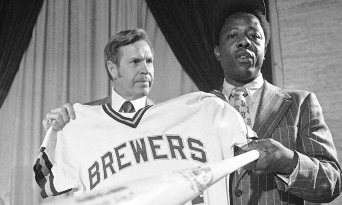 Milwaukee Brewers manager Del Crandall (L) and Henry Aaron display Aaron's new Brewers jersey and a bat during a news conference in Milwaukee to announce signing Aaron, on Nov. 14, 1974. (Paul Shane/AP Photo)