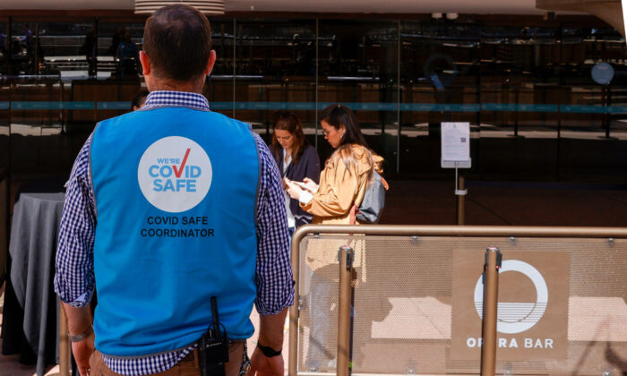 A COVID safe coordinator looks on outside the Opera Bar at Sydney Opera House on Sept. 10, 2020, in Sydney, Australia. (Jenny Evans/Getty Images)
