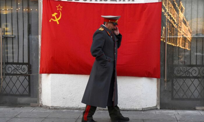An impersonator of Soviet leader Joseph Stalin walks past a hammer-and-sickle red flag in central Moscow on Nov. 21, 2016. (Vasily Maximov/AFP via Getty Images)