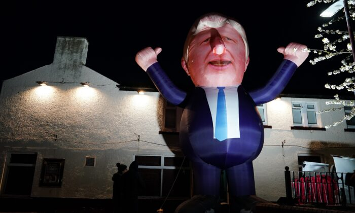 People walk past a giant inflatable representation of Prime Minister Boris Johnson outside the Mill House Leisure Center where the count process for the Parliamentary by-election is taking place in Hartlepool, England, on May 7, 2021. (Ian Forsyth/Getty Images)