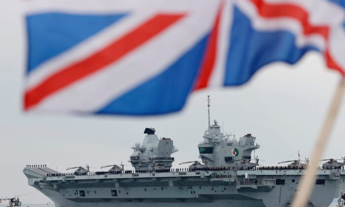 The HMS Queen Elizabeth aircraft carrier leaves Portsmouth Naval Base on the south coast of England on May 1, 2021. The carrier will take part in exercises off Scotland before heading to the Indo-Pacific region for her first operational deployment. (Adrian Dennis/AFP via Getty Images)