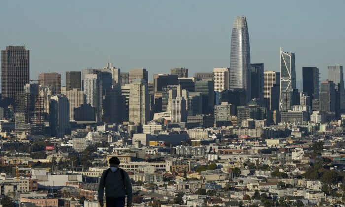 A man walks in front of the skyline on Bernal Heights Hill during the coronavirus pandemic in San Francisco on Dec. 7, 2020. (Jeff Chiu/AP Photo)