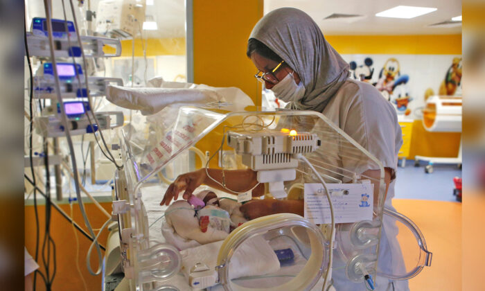 A Moroccan nurse takes care of one of the nine babies protected in an incubator at the maternity ward of the private clinic of Ain Borja in Casablanca, Morocco. (Abdeljalil Bounhar/AP Photo)