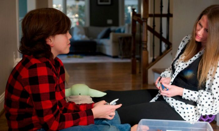Daniel Mooney, a third-grader who attends classes virtually from his basement because his public school is closed due to the Covid-19 pandemic, plays with his mother Courtney Mooney at their home in Falls Church, Va., on Feb. 4, 2021. (Bastien Inzaurralde/AFP via Getty Images)