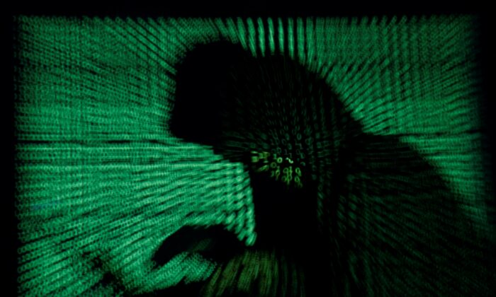 A hooded man holds a laptop computer as cyber code is projected on him in this illustration picture taken on May 13, 2017. (Kacper Pempel/Reuters, Illustration/File Photo)