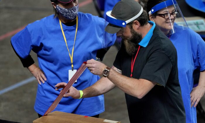 Maricopa County ballots cast in the 2020 general election are unsealed to be examined and recounted by contractors working under a contract with the Arizona Senate, at Veterans Memorial Coliseum in Phoenix, on May 6, 2021. (Matt York/AP Photo/Pool)