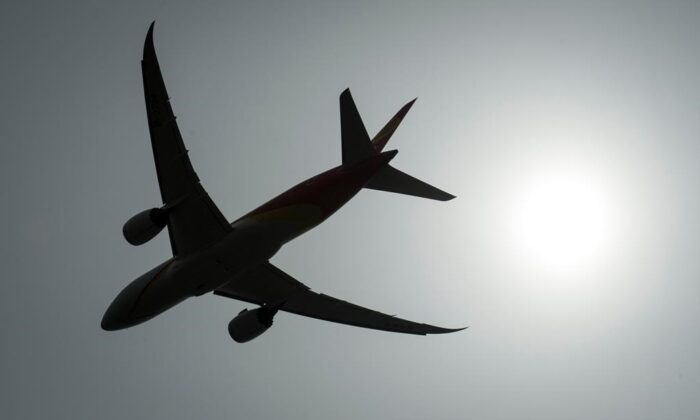 A plane is silhouetted as it takes off from Vancouver International Airport in Richmond, B.C., on May 13, 2019. (The Canadian Press/Jonathan Hayward)