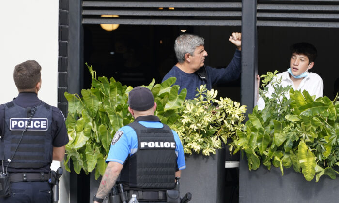 Shoppers look from a restaurant as police officers enter the Aventura Mall after a shooting left three people injured and several suspects in custody, in Aventura, Fla., on May 8, 2021. (Marta Lavandier/AP Photo)