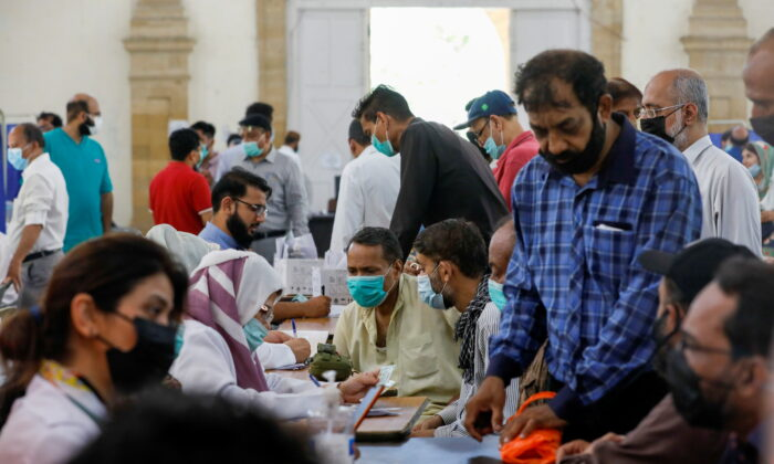 People gather to receive their CCP virus disease (COVID-19) vaccine doses, at a vaccination center in Karachi, Pakistan, on April 28, 2021. (Akhtar Soomro/Reuters)