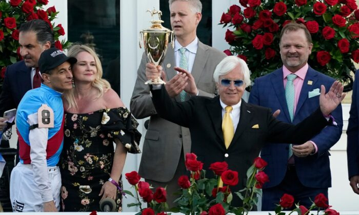 Jockey John Velazquez (L) watches as trainer Bob Baffert holds up the winner's trophy after they victory with Medina Spirit in the 147th running of the Kentucky Derby at Churchill Downs,  in Louisville, Ky., on May 1, 2021. (Jeff Roberson/AP Photo)