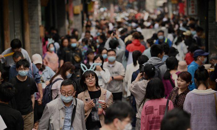 People walk through an alley near Houhai lake in Beijing, China, on May 4, 2021. (Noel Celis/AFP via Getty Images)