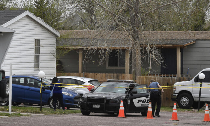 A Colorado Springs police officer goes to help a person who was in a different mobile home to be able to get to her car from behind the crime tape in Colorado Springs, Colo., on May 9, 2021. (Jerilee Bennett/The Colorado Springs Gazette via AP)