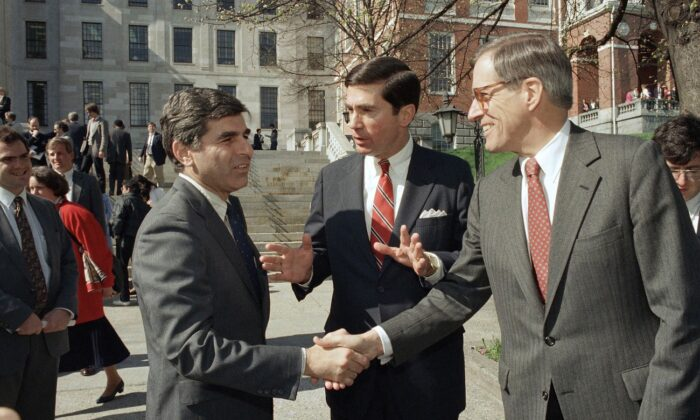 Massachusetts Governor Michael Dukakis (L) shakes the hands of former Delaware Governor Pierre Du Pont (R) as former Virginia Governor Charles S. Robb looks on, after both men attended the Jobs for Bay State Grads program in Boston, Mass., on April 27, 1987. (Jim Shea/AP Photo)