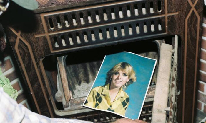 A law enforcement official discovers a photograph of Pamela Pitts in the wood stove of a home she shared with two others in Prescott, Ariz., in 1988. (Yavapai County Sheriff's Office via AP)