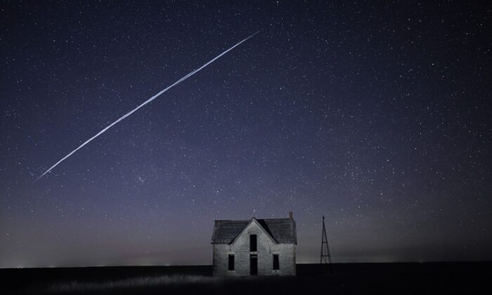 A string of SpaceX StarLink satellites passes over an old stone house near Florence, Kan., on May 6, 2021. (Reed Hoffmann/AP Photo)