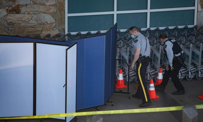 RCMP officers search around rows of luggage carts as screens block off an area of the sidewalk after a shooting outside the international departures terminal at Vancouver International Airport, in Richmond, B.C., on May 9, 2021. (Darryl Dyck / The Canadian Press)