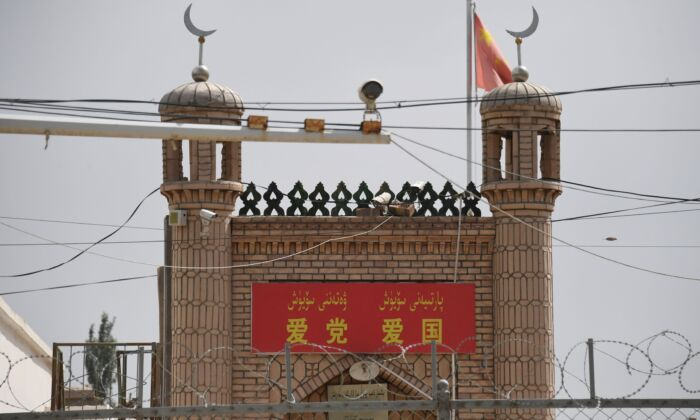 """The Jieleixi No.13 village mosque with slogans """"Love the [Chinese Communist] Party, Love China,"""" in Yangisar, south of Kashgar, in China's western Xinjiang region on June 4, 2019. (Greg Baker/AFP via Getty Images)"""