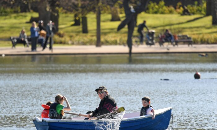 Children are rowed across the lake in the spring sunshine in Victoria Park, east London, on April 22, 2021. (Daniel Leal-Olivas/AFP via Getty Images)