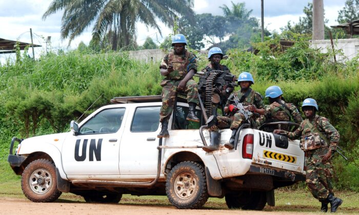 Blue helmet members of the United Nations Organization Stabilization Mission in the Democratic Republic of Congo MONUSCO sit on the back of a U.N. pick-up truck in Beni in a file photo. (Alain Wandimoyi/AFP via Getty Images)