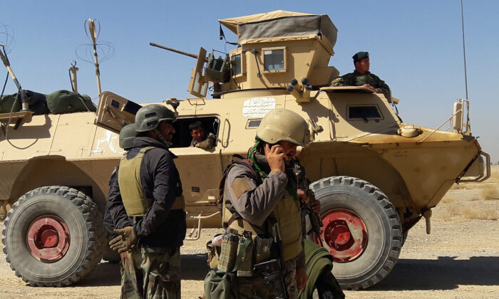 Afghan security forces stand near an armoured vehicle during ongoing fighting between Afghan security forces and Taliban fighters in the Busharan area on the outskirts of Lashkar Gah, the capital city of Helmand province May 5, 2021. (Sifatullah Zahidi/AFP via Getty Images)
